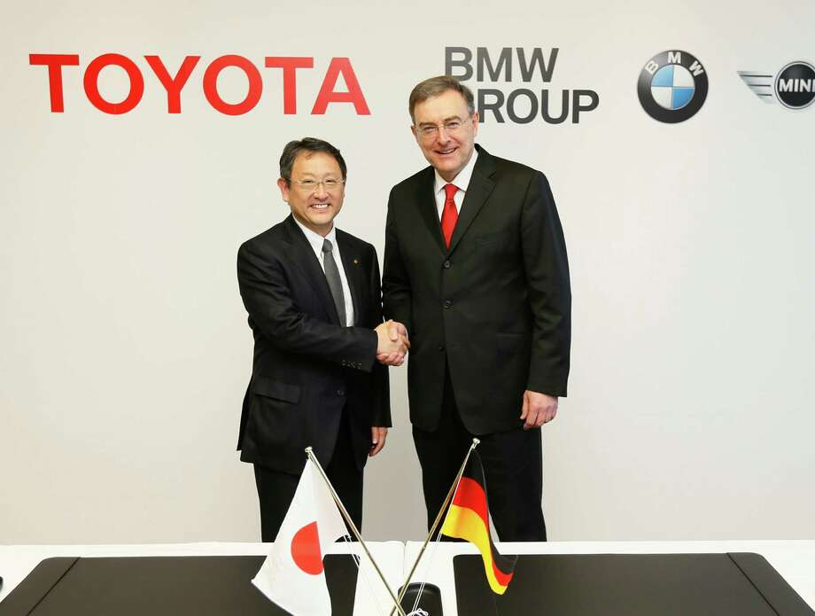 "In this photo released by Toyota Motor Corp., Toyota President Akio Toyoda, left, shakes hands with BMW AG chief executive Norbert Reithofer during a signing ceremony to jointly develop next-generation batteries for green vehicles in Nagoya, central Japan, Thursday, Jan. 24, 2013.  Toyota and BMW are working together on next-generation batteries for green vehicles called ""lithium-air"" as their collaboration, first announced in late 2011, moves ahead in fuel cells, sports vehicles and other fields. (AP Photo/Toyota Motor Corp.) EDITORIAL USE ONLY"