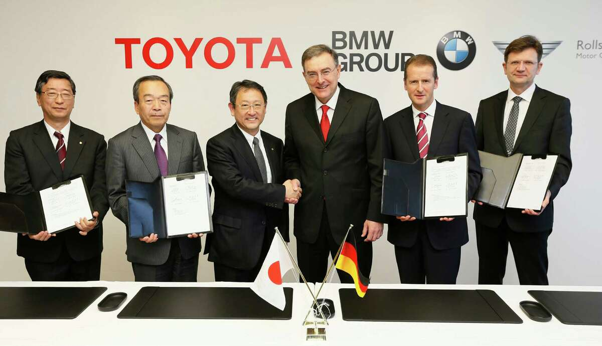 In this photo released by Toyota Motor Corp., Toyota President Akio Toyoda, third left, shakes hands with BMW AG chief executive Norbert Reithofer, third right, as their executives show signed documents during a signing ceremony to jointly develop next-generation batteries for green vehicles in Nagoya, central Japan, Thursday, Jan. 24, 2013. Toyota and BMW are working together on next-generation batteries for green vehicles called