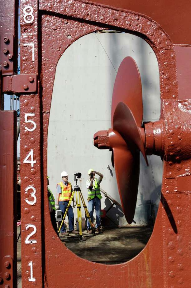Shown through the propellor, Travis Davis, left, maintenance supervisor for Battleship Texas, holds a a Leica HDS7000 laser scanner as Richard Lasater, right, president of SmartGeoMetrics, takes photos to document color as part of his laser scanning work to produce a 3D representation of Elissa. Photo: Melissa Phillip, Houston Chronicle / © 2013 Houston Chronicle