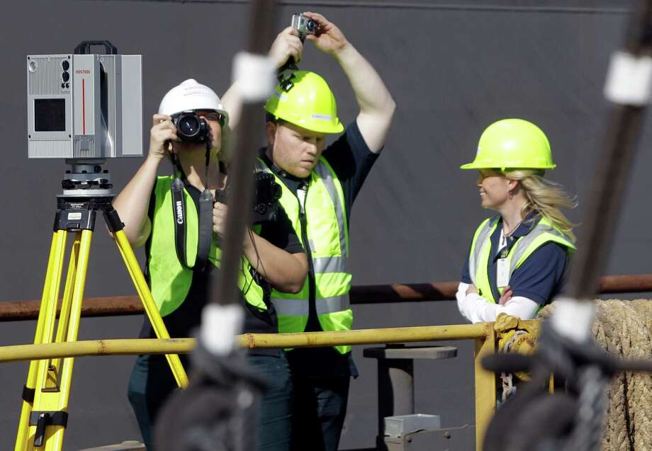 Barbara Misto, left, logistics manager of  SmartGeoMetrics, takes photos as Nicholas Boccio, center, chief technologist, adjusts a hardhat mounted camera as they and Virginia Morrill, project manager, use a Leica HDS7000 laser scanner, shown left, to produce a 3D representation of Elissa in dry dock at Bollinger Shipyards. Photo: Melissa Phillip, Houston Chronicle / © 2013 Houston Chronicle