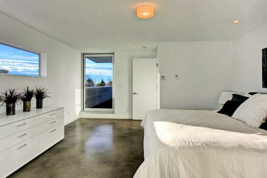 Master bedroom of 3208 44th Ave. W. The 3,496-square-foot house, built in 2012, has five bedrooms, 3.5 bathrooms, walls of windows, a den/office, a family room, a bar, concrete floors, a rooftop deck, a front porch, a patio, views of Puget Sound and the Olympic Mountains and a two-car garage on a 5,800-square-foot lot. It's listed for $1.575 million. Photo: Vista Estate Imaging/Courtesy Enrico Pozzo/Coldwell Banker Bain
