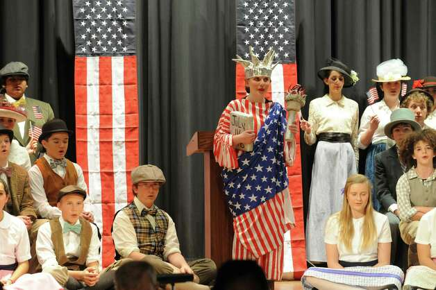 Emily Bass dressed as the Statue of Liberty during the eighth grade's production of âÄúThe Music ManâÄù at Eastern Middle School in Greenwich, Conn., Thursday, Jan. 24, 2013. The show continues Friday and Saturday at 7:30 p.m. at the school, 51 Hendrie Ave. Tickets will be on sale in the main lobby before school. Tickets are $15 each for the Friday and Saturday evening performances.30 p.m. at the school, 51 Hendrie Ave. Tickets will be on sale in the main lobby before school. Tickets are $5 each for the Thursday performance and $15 each for the Friday and Saturday evening performances. Photo: Helen Neafsey / Greenwich Time