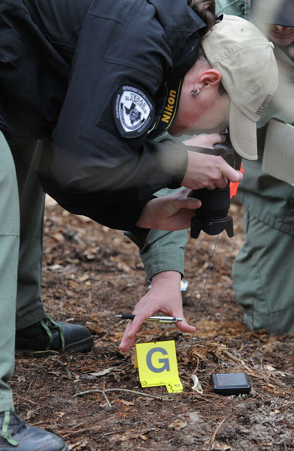 Wende Wakeman Texas Ranger photographs a bone discovered north of Jasper Thursday afternoon. Rangers and Jasper Deputies have been combing the area after a man's skull was found on Tuesday. Photo taken Guiseppe Barranco/The Enterprise Photo: Guiseppe Barranco, STAFF PHOTOGRAPHER / The Beaumont Enterprise