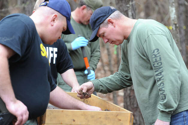 Officials search of bones Thursday in a area where a man's skull was found north of Jasper on Tuesday. Working in tandem with the Jasper Sheriff's Office, the Texas Rangers spent part of Thursday sifting through dirt and foliage finding several other bones. It has not been determined that the bones are human.  Photo taken Thursday, January 23, 2013 Guiseppe Barranco/The Enterprise Photo: Guiseppe Barranco, STAFF PHOTOGRAPHER / The Beaumont Enterprise