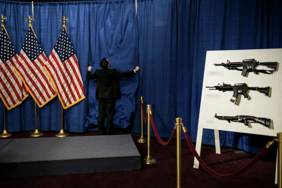 """A staff member prepares for a news conference Thursday on Capitol Hill, where House and Senate Democrats were joined by law enforcement officials to introduce the """"Assault Weapons Ban of 2013"""" legislation."""