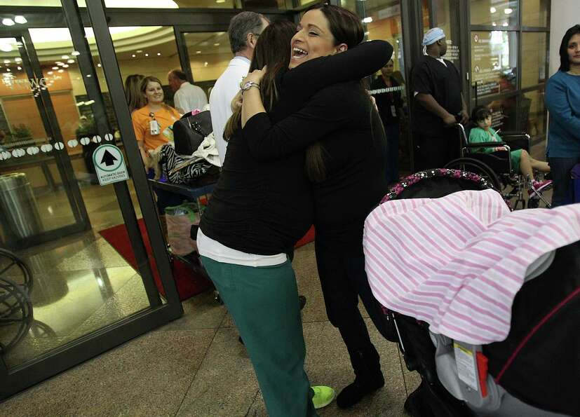 Ashley Cardenas smiles while embracing Physical Therapist Emily Hermes after being discharged from T