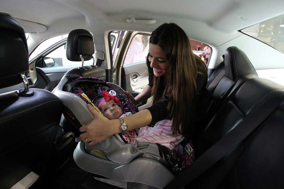 """It's your first car ride"" says Ashley Cardenas to her daughter Audrina Cardenas, 3 months, after being discharged from Texas Children's Hospital. Photo: Mayra Beltran, Houston Chronicle / © 2013 Houston Chronicle"