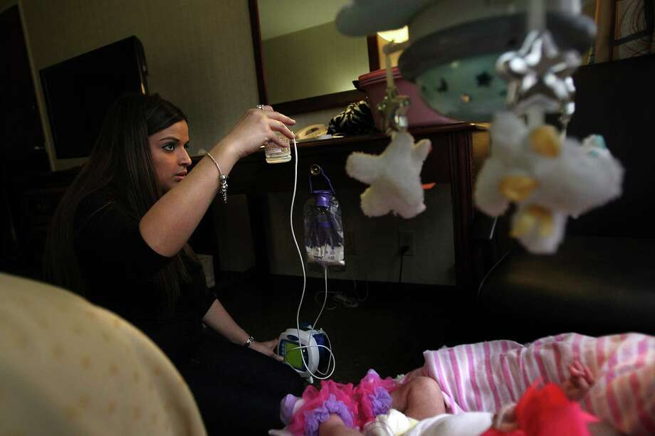 Ashley Cardenas feeds daughter Audrina Cardenas in a local hotel where they'll be staying in order for doctors to continue monitoring her for a couple of weeks. Photo: Mayra Beltran, Houston Chronicle / © 2013 Houston Chronicle