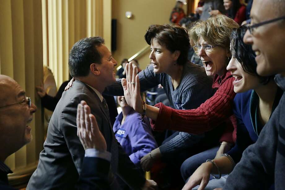 Rhode Island state Rep. Frank Ferri (center) and his partner, Tony Caparco (left), greet supporters of the same-sex marriage bill. The measure now goes to the state Senate. Photo: Steven Senne, Associated Press