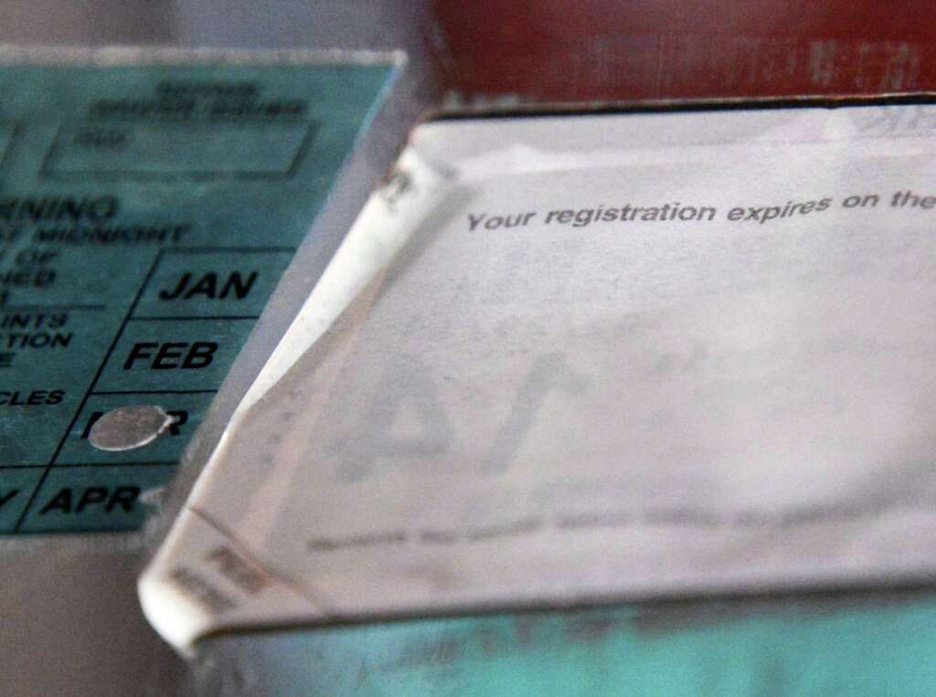 The edges of a NYS automobile registration sticker begin to crul up on a car in