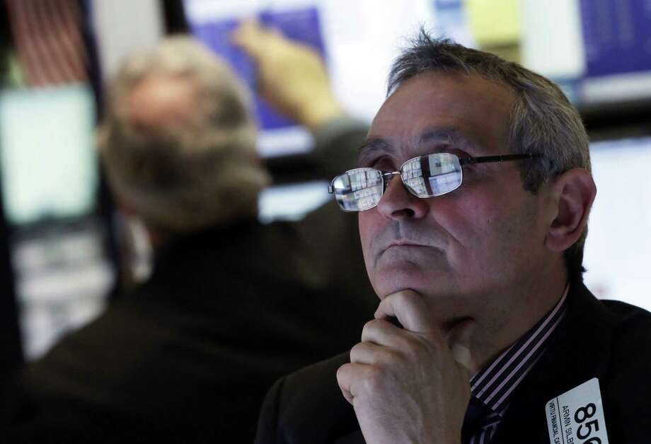 In this Wednesday, Jan. 23, 2013 photo, the screens of specialist Armin Silbersmith are reflected in his glasses as he works at his post on the floor of the New York Stock Exchange. Europe's stock markets were broadly higher Thursday Jan. 23, 2013 amid signs the continent's services and manufacturing slump was easing.  (AP Photo/Richard Drew) Photo: Richard Drew