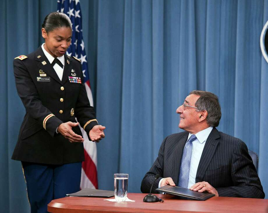 Army Lt. Col. Tamatha Patterson, of Huntingdon, Tenn., waits for Defense Secretary Leon Panetta to hand her the memorandum he has just signed ending the 1994 ban on women serving in combat, Thursday, Jan. 24, 2013,  during a news conference at the Pentagon. (AP Photo/Cliff Owen) Photo: Cliff Owen