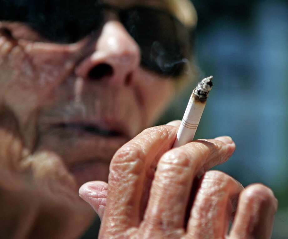 FILE - In a June 11, 2007 file photo, Helen Heinlo smokes outside of a coffee shop in Belmont, Calif. Millions of smokers could be priced out of health insurance because of tobacco penalties in President Barack Obama's health care law, say experts. The Affordable Care Act allows health insurers to charge smokers buying an individual policy up to 50 percent higher premiums starting next Jan. 1. For a 55-year-old smoker, the penalty could reach nearly $4,250 a year. A 60-year-old could wind up paying nearly $5,100 on top of premiums. (AP Photo/Paul Sakuma, File) Photo: Paul Sakuma
