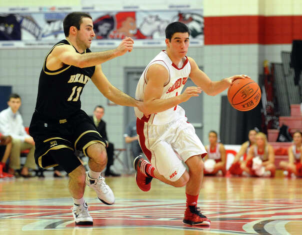 Sacred Heart's #4 Phil Gaetano moves the ball as Bryant's #11 Shane McLaughlin tracks, during men's basketball action at Sacred Heart University in Fairfield, Conn. on Thursday January 24, 2013. Photo: Christian Abraham / Connecticut Post