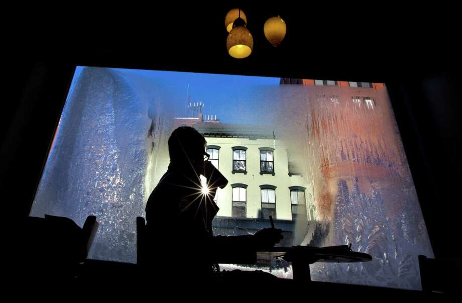 Erin Leighton sips a coffee while seated next to a frost-covered window at a coffee shop, Thursday, Jan. 24, 2013, in Portland, Maine.  An arctic cold front with sub-zero temperatures continues to grip the region. Photo: Robert F. Bukaty, Associated Press / AP