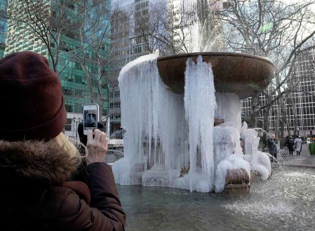 A woman pauses to take a photograph of the frozen fountain in New York's Bryant Park, in mid-town Manhattan, Thursday, Jan. 24, 2013.  A  cold wave with sub-zero temperatures is expected to keep its icy grip on much of the eastern U.S. into the weekend before seasonable temperatures bring relief. Photo: Richard Drew, Associated Press / AP