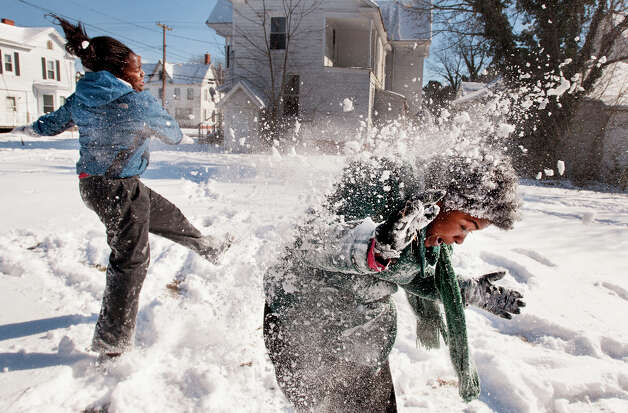 Satoria Ginn, left, throws snow at Desiree Lyons during a snow battle Thursday morning Jan. 24, 2012, along Laurel Street in Pocomoke City, Md. The snow was very dry making snowballs hard to make, so they settled for throwing snow at each other. (AP Photo/The Daily Times, Grant L. Gursky)  NO SALES Photo: Grant L. Gursky, Associated Press / The Daily Times