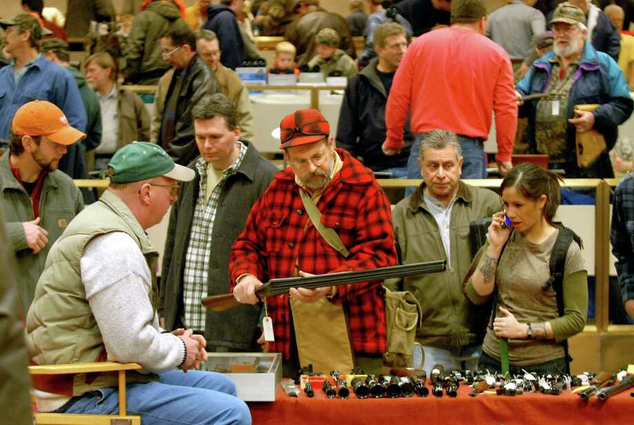 Michael Thomas of Kingston, center in red plaid, looks over an AH Fox double barrel shotgun Saturday, Jan. 20, 2007, during a gun show at the Empire State Plaza Convention Center in Albany, N.Y. (Cindy Schultz/Times Union archive) Photo: CINDY SCHULTZ / ALBANY TIMES UNION
