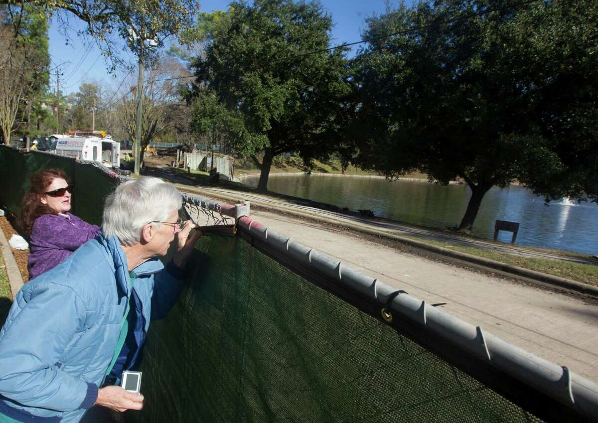 Memorial Thicket residents Phil Richardson and Geralyn Cornelius peek over a fence at their beloved Lake Thicket.