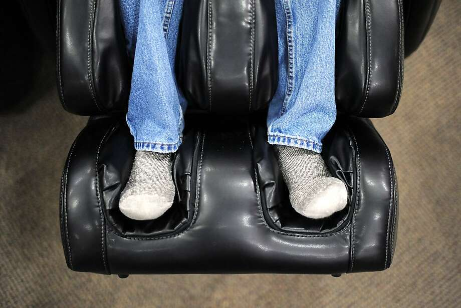 A customer with his shoes off is less inclined to run out of a sales pitch for the $3,299 uAstro massage chair. Photo: Michael Short, Special To The Chronicle