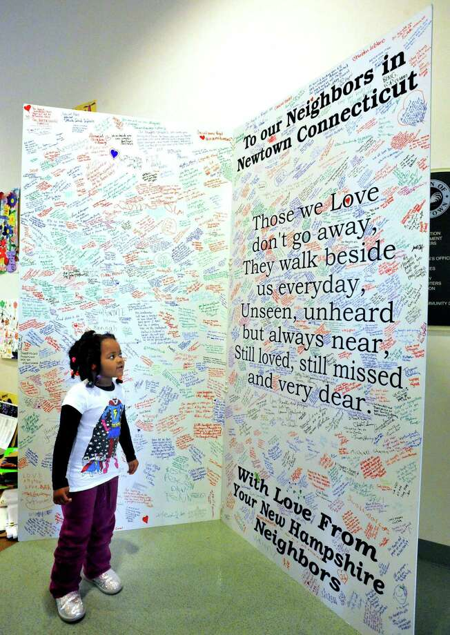 Porshea Jackson, 4, who came with her grandparents from South Carolina to deliver  a banner honoring the Sandy Hook victims, looks at a giant sympathy card in the gallery of condolences in Newtown Town Hall Thursday, Jan. 24, 2013. Photo: Michael Duffy