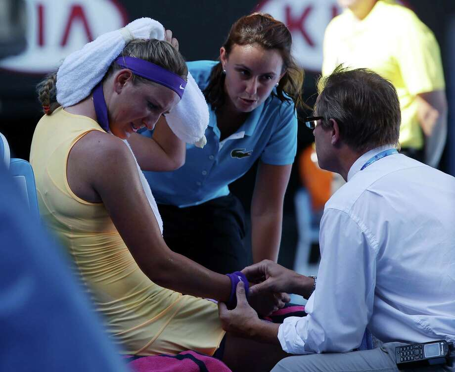 Victoria Azarenka receives treatment for chest pains during her semifinal against Sloane Stephens. The match was stopped for nine minutes Thursday. Photo: Aaron Favila, STF / AP