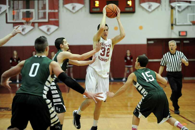 Scotia's Dom LeMorta (32), center, looks to pass during their basketball game against Hudson Falls o