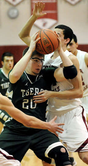 Hudson Falls Connor West (20), left, pushes to the hoop as Scotia's Mike Palleschi (44) defends duri