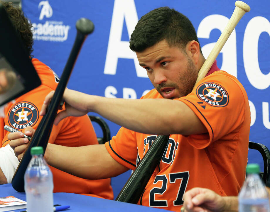Houston Astros player Jose Altuve juggles bats being signed as he and  Brett Wallace sign autographs with J.R. Richard and broadcaster Bill Brown at the Academy Sports and Outdoors store at 1604 near Gold Canyon on January 24, 2013. Photo: Tom Reel, Express-News / ©2012 San Antono Express-News