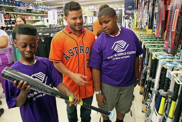 Houston Astros player Jose Altuve helps Boys and Girls Clubs participants Rashad Henderson (left) and Corey Swan select a good bat as they shop before he and Brett Wallace sign autographs with J.R. Richard and broadcaster Bill Brown at the Academy Sports and Outdoors store at 1604 near Gold Canyon on January 24, 2013. Photo: Tom Reel, Express-News / ©2012 San Antono Express-News