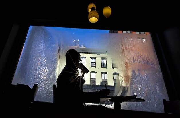 Erin Leighton sips a coffee while seated next to a frost-covered window at a coffee shop, Thursday, Jan. 24, 2013, in Portland, Maine.  An arctic cold front with sub-zero temperatures continues to grip the region.  Photo: Robert F. Bukaty, Associated Press