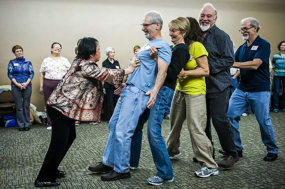 "Dr. Effie Poy Yew Chow, left, demonstrates ""Qi"", or internal breath energy by pushing backward, from left, Myron Levinson, Mo Kremer, Jaimie Arkelian, Tim Nigh and Karl Tray, during a workshop at Harry S. Truman Memorial Veterans' Hospital Saturday, Jan. 19, 2013, in Columbia, Mo. Photo: August Kryger, Associated Press"