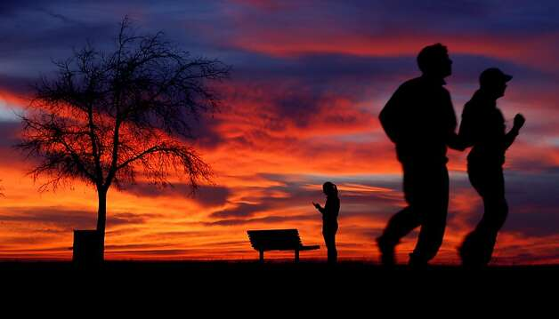 People jog along the shore of Lake Hefner just after sunset in Oklahoma City, Wednesday, Jan. 23, 2013.  Photo: Bryan Terry, Associated Press