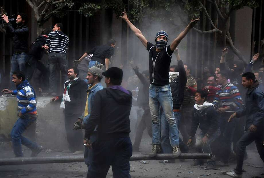 Egyptian protesters try to tear down a cement wall built to prevent them from reaching parliament and the Cabinet building near Tahrir Square, in Cairo, Egypt, Thursday, Jan. 24, 2013. Egypt's black-clad riot police fired tear gas in fierce dawn clashes with dozens of protesters. The violence which was soothed hours later in central Cairo comes on eve of the second anniversary of Egypt's Jan. 25 uprising, which toppled longtime authoritarian president Hosni Mubarak in 2011.  Photo: Hussein Tallal, Associated Press