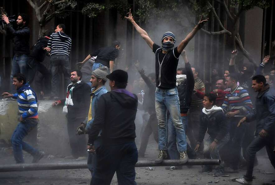 Egyptian protesters try to tear down a cement wall built to prevent them from reaching parliament an