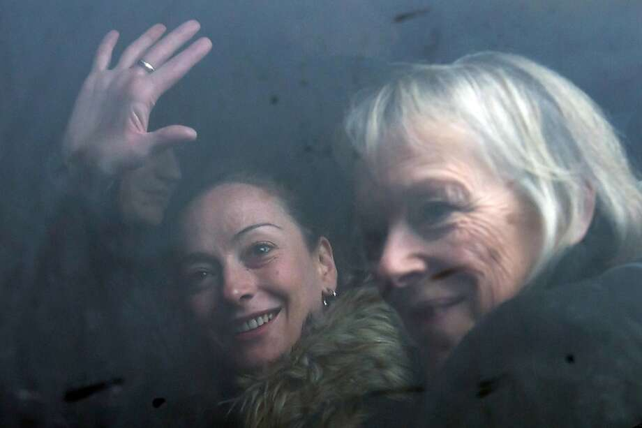 France's Florence Cassez (L) gestures, next to her mother Charlotte, from a minivan at Roissy airport on January 24, 2013 in Roissy-en-France where she landed after being freed from a Mexican prison the day before following a Supreme Court ruling that police violated her rights by staging her arrest for kidnapping on national television seven years ago. After facing 60 years in jail, Cassez, 38, took a flight to Paris, hours after three of five justices voted for her immediate release in a case that had strained Franco-Mexican ties.  Photo: Bertrand Langlois, AFP/Getty Images