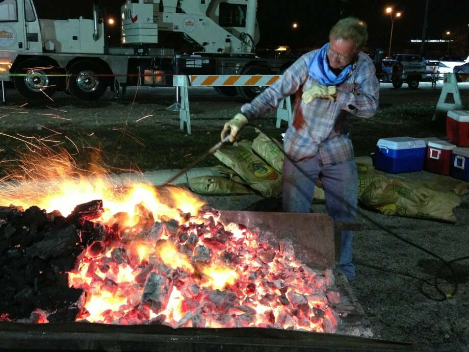 Dickie Dziuk tends to a charcoal fire for cooking during the 35th annual Cowboy Breakfast at Cowboys Dance Hall on Friday, Jan. 25, 2013. The outdoor breakfast for thousands traditionally kicks off the San Antonio Stock Show and Rodeo. Photo: Billy Calzada, San Antonio Express-News / SAN ANTONIO EXPRESS-NEWS