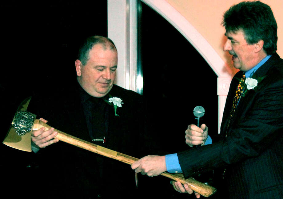 Chief Jim Ferlow, right, presents outgoing Chief Jeff Emmons with the ceremonial axe in recognition of his leadership during Water Witch Hose Co. No. 2's annual awards dinner at the Candlewood Inn in Brookfield. Jan. 12, 2013 Photo: Walter Kidd