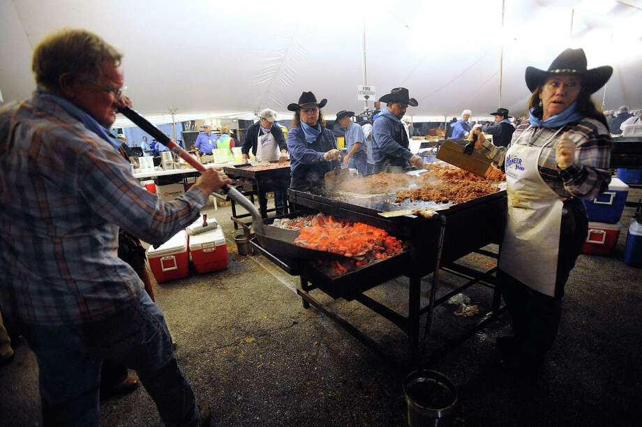 Dickie Dziuk, left, delivers glowing briquets as Sarah Mosher, right, prepares ground beef for tacos  during the 35th annual Cowboy Breakfast at Cowboys Dance Hall on Friday, Jan. 25, 2013. Several thousand people turned out for the event, which traditionally kicks off the San Antonio Stock Show & Rodeo, for free tacos, biscuits, coffee and tamales. Photo: Billy Calzada, San Antonio Express-News / SAN ANTONIO EXPRESS-NEWS