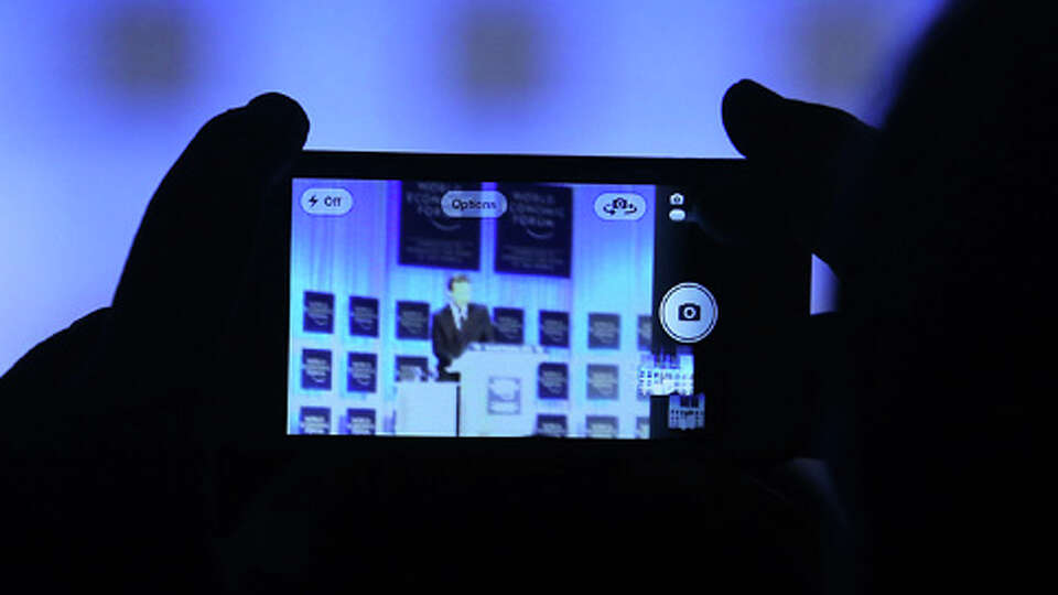 An attendee uses an Apple Inc. iPhone to take a photograph of David Cameron, U.K. prime minister, sp