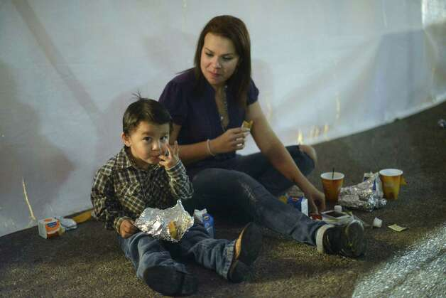 Sara White and her son, Mikey, 2, eat tamales and egg tacos during the 35th annual Cowboy Breakfast at Cowboys Dance Hall on Friday, Jan. 25, 2013. Several thousand people turned out for the event, which traditionally kicks off the San Antonio Stock Show & Rodeo, for free tacos, biscuits, coffee and tamales. Photo: Billy Calzada, San Antonio Express-News / SAN ANTONIO EXPRESS-NEWS