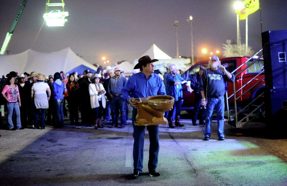 Chuck Christian, chairman of the 35th annual Cowboy Breakfast, carries a toilet to be used in the cowchip tossing contest at Cowboys Dance Hall on Friday, Jan. 25, 2013. Several thousand people turned out for the event, which traditionally kicks off the San Antonio Stock Show & Rodeo, for free tacos, biscuits, coffee and tamales. Photo: Billy Calzada, San Antonio Express-News / SAN ANTONIO EXPRESS-NEWS