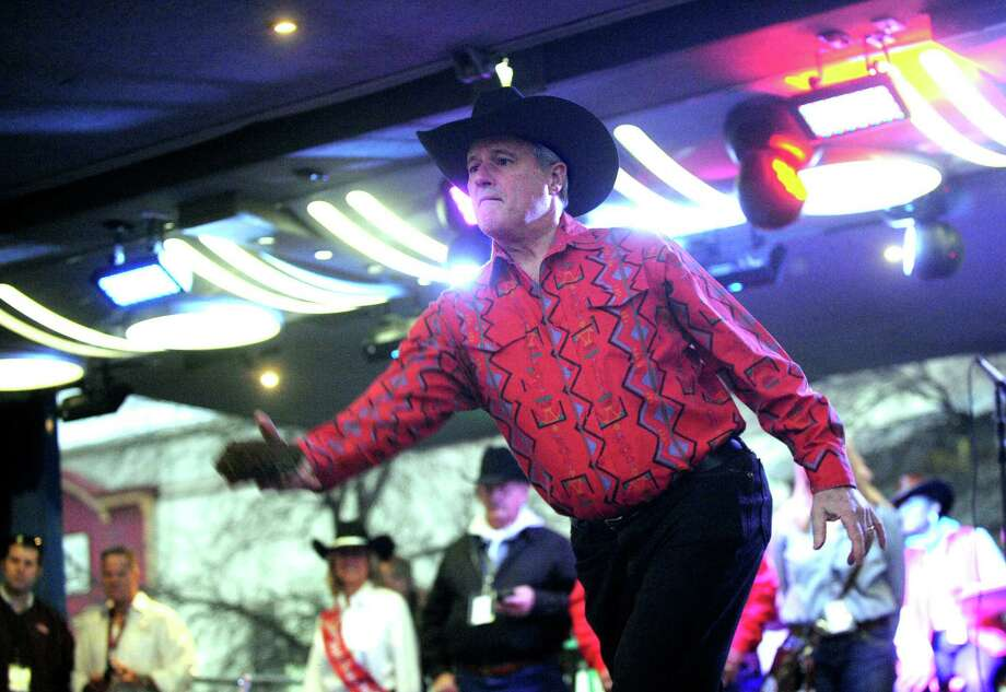 Bexar County Commissioner Tommy Adkisson tosses the winning cowchip during a contest at the 35th annual Cowboy Breakfast at Cowboys Dance Hall on Friday, Jan. 25, 2013. Photo: Billy Calzada, San Antonio Express-News / SAN ANTONIO EXPRESS-NEWS