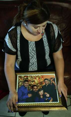 Monica Guevara holds a Christmas family portrait made just a month ago, which includes her son Roger Rodriguez Jr., above right, 17, who was killed close to his home. Thursday, Jan. 24, 2013. Photo: Bob Owen, San Antonio Express-News / © 2012 San Antonio Express-News