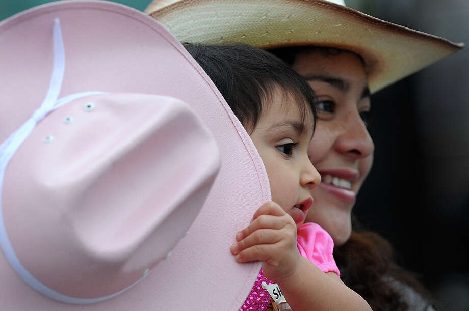 Dennise Lozano and her child, Lilianna, 18 months, stroll the grounds during the 35th annual Cowboy Breakfast at Cowboys Dance Hall on Friday, Jan. 25, 2013. Several thousand people turned out for the event, which traditionally kicks off the San Antonio Stock Show & Rodeo, for free tacos, biscuits, coffee and tamales. Photo: Billy Calzada, San Antonio Express-News / SAN ANTONIO EXPRESS-NEWS