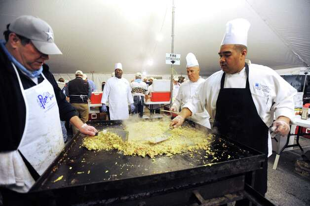 Bill Burke, left, Rod Wagner and Paris Barnes prepare tacos during the 35th annual Cowboy Breakfast at Cowboys Dance Hall on Friday, Jan. 25, 2013. Several thousand people turned out for the event, which traditionally kicks off the San Antonio Stock Show & Rodeo, for free tacos, biscuits, coffee and tamales. Photo: Billy Calzada, San Antonio Express-News / SAN ANTONIO EXPRESS-NEWS