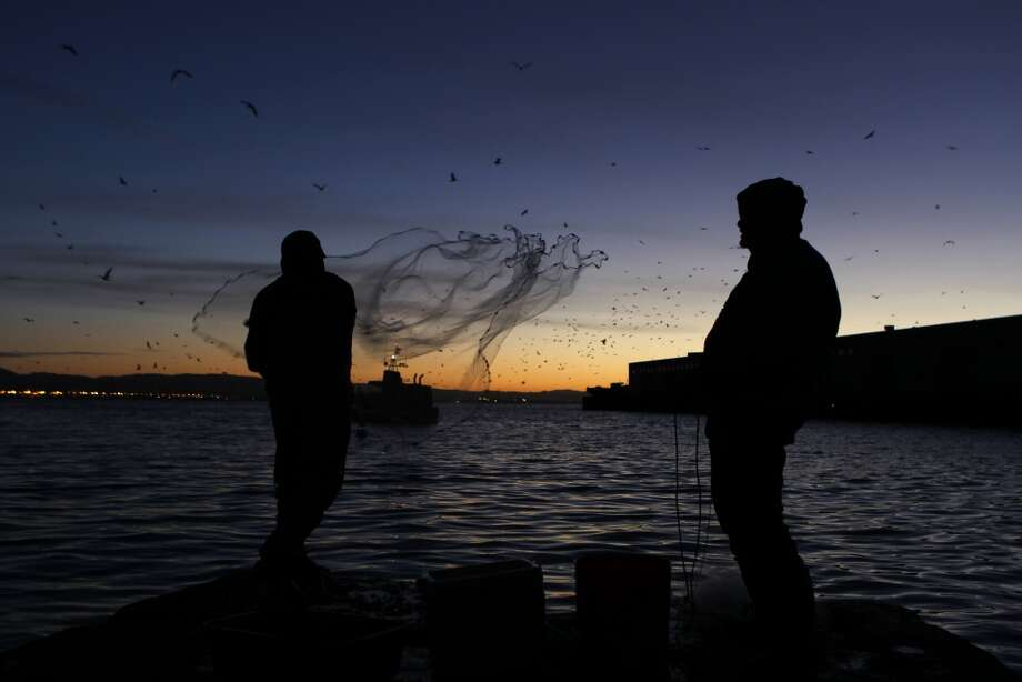 Rudy Domingo (left) casts a net into the bay while fishing for herring with Francis Reyes (right) off China Basin before sunrise in San Francisco.