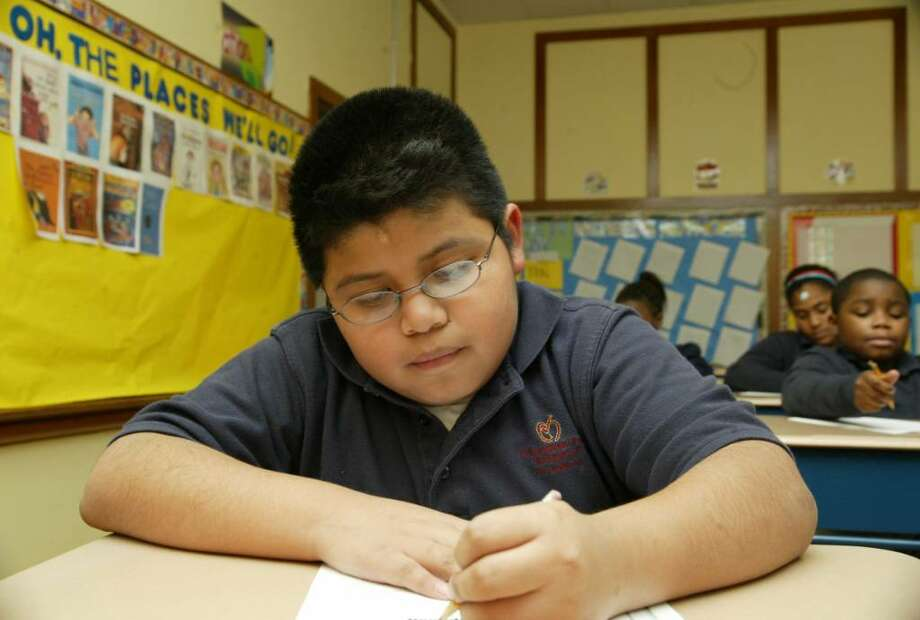 Mario Cuatzo, a fourth grade student at the Achievement First Bridgeport Middle School in Bridgeport works in Miss Emily Saunder's classroom at the school. Tuesday, Dec. 22, 2009. Photo: Phil Noel / Connecticut Post