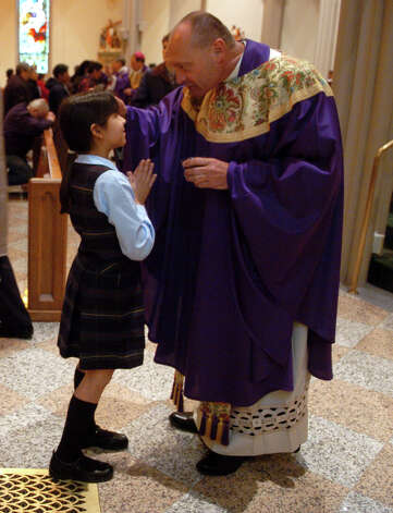 During the noontime Ash Wednesday mass at St. Augustine's Cathedral in Bridgeport, Conn. on Feb. 6th, 2008, Monsignor Kevin Wallin, Pastor at St. Augustine's, distributed ashes to the students of St. Augustine School. Photo: File Photo/Tracy Deer-Mirek, File Photo / Connecticut Post File Photo