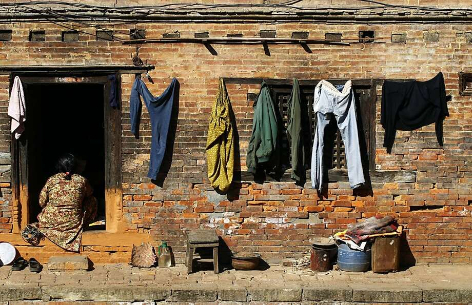Laundry day: A woman sits in her doorway in Bhaktapur, Nepal. Photo: Niranjan Shrestha, Associated Press